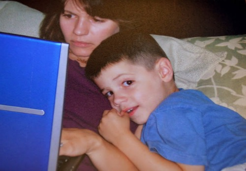 Author Caroline Starr Rose works on a manuscript while her son looks on. Learn how she became a published author on the Brilliant Business Moms Podcast.