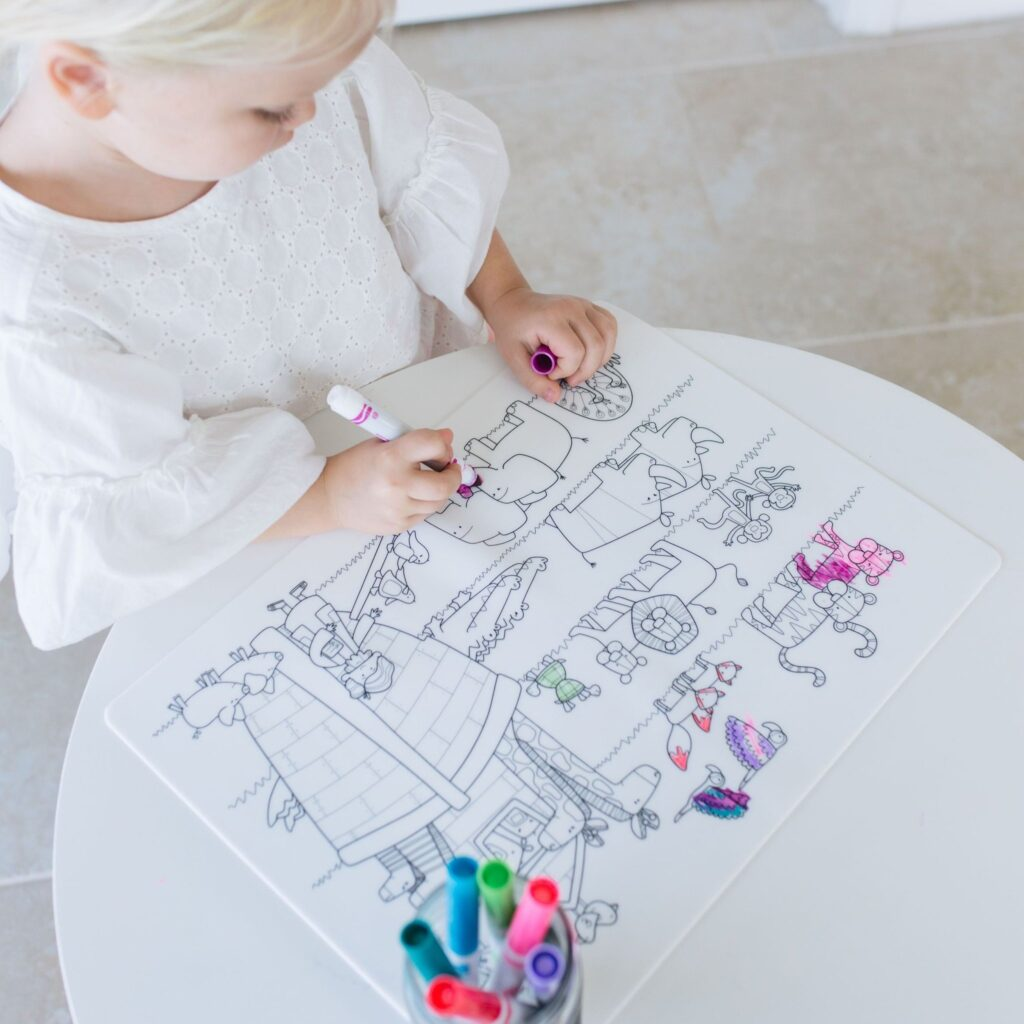 child coloring with markers on a silicone mat with picture of Noahs Ark